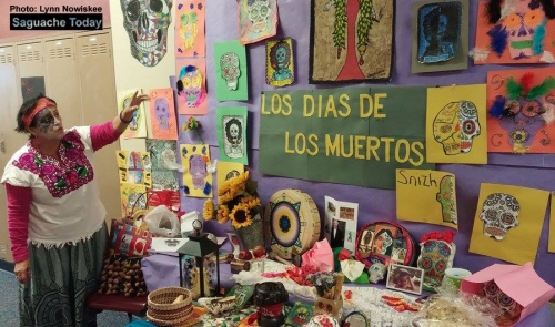 Senora Garcia explains the meaning behind the elaborate Los Dias de Los Muertes altar on display at the Mountain Valley School last week. Students learned about this special Mexican holiday. Photo: Lynn Nowiskee/Saguache Today.