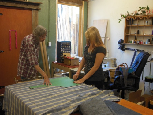Project coordinator Penny Bruce (left) with student intern Marion select appropriate colors and materials as pattern pieces to create reversible, one-of-kind tote bags in a variety of sizes and styles.