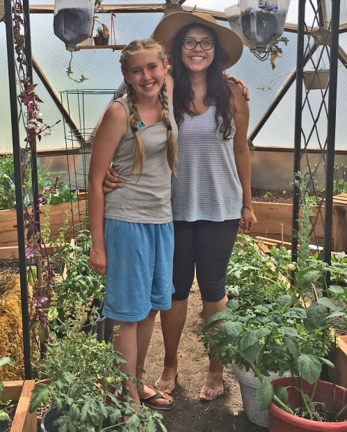 Megan Cleaver, right, stands with seventh-grader Laura Morfitt, in the greenhouse at Mountain Valley School in Saugache, where Megan helped get the greenhouse up and running. Photo: CDE