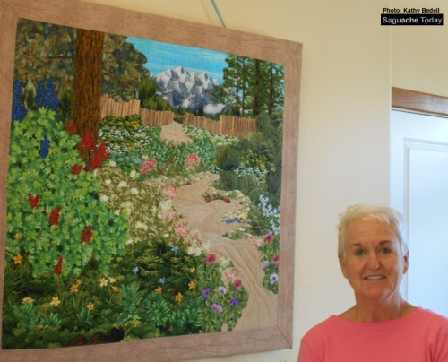 Landscape quilter and instructor Pam Jernigan stands next to the quilt that started it all inspired from a garden in Crestone! Photo: Saguache Today/Kathy Bedell
